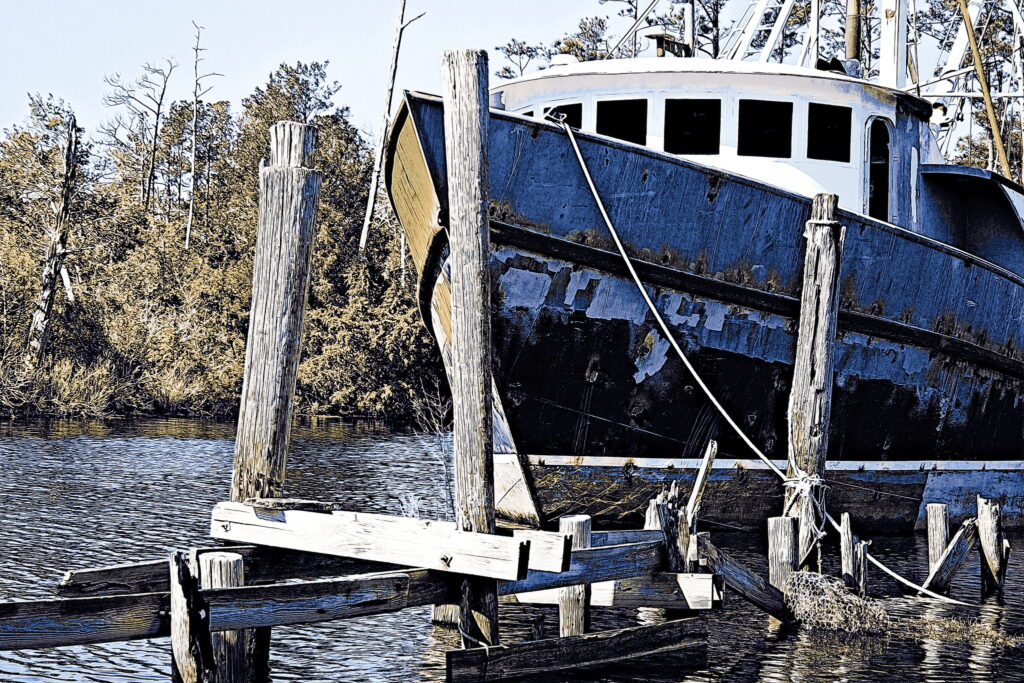 A purse seiner, stripped of paint and gear, refitting at Bayboro.