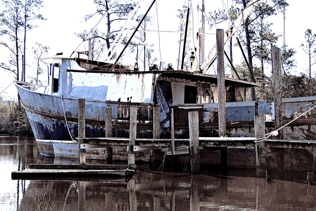 A hard-worn purse seiner lies at a decaying dock in Bayboro, waiting for refit. The boat has been stripped of gear and her paint is in patches.